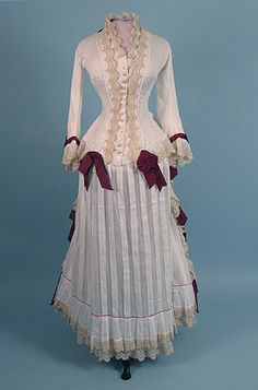 Day dress, 1870's.  The dark red ribbons are set off nicely against the white fabric.