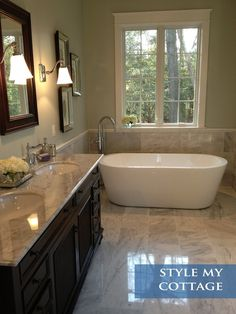 Master bathroom: Light grey granite, dark cabinets and mirror, light tile, light walls, silver decor and fixtures