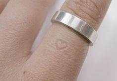 its not really a tattoo...... but its permanent on your skin. you see..... the longer you wear the ring, the heart will permanently imprint itself on your finger. even without wearing it, it will still be there