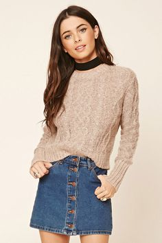 A cable knit sweater with ribbed trim, a crew neckline, and long sleeves.