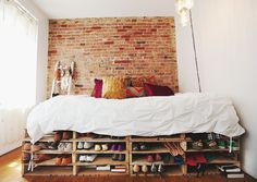 If you love shoes but struggle to store them, try stacking wooden shipping pallets like this NYC studio apartment. It's a cute and clever way to display shoes, and it turns the bed into a focal point. Photo by Chellise Michael via Homepolish