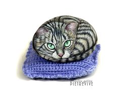 Beautiful hand painted kitty.  It is a smooth pebble, hand painted using acrylics, sealed with a matt protective finish and signed by the artist on