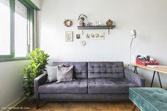 Sala de estar tem sofá cinza, parede galeria e prateleira alta.