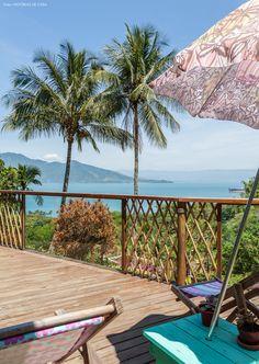 Poltronas e guarda sol com tecidos estampados na varanda dessa casa de praia em Ilhabela.