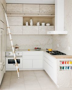 """To complement the white-washed custom cabinetry in her kitchen, architect Julie Salles Schaffer designed a tile backsplash to resemble """"melting butter in a white pan"""". Daltile arranged her two-color AutoCAD design—white and off-white—onto a mesh backing for a small fee. To soften the edges of the cabinets' drawers and doors, Schaffer requested radial edging."""
