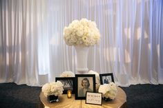 Floral Centerpiece with Framed Photographs |   Photography: Rob and Wynter Photography.   Read More:  http://www.insideweddings.com/weddings/mlb-players-white-black-gold-nye-ballroom-wedding-in-atlanta/806/