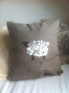 Pillow case with sheep made out of white buttons