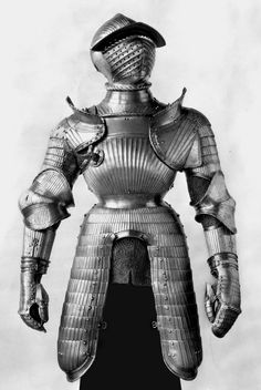 The helmet, pauldrons (shoulder defenses), and vambraces (arm defenses) of this armor are attributed to Kolman Helmschmid based on comparison with his known works. The helmet's distinctive snub-nosed visor appears to be a form that he originated and used on three other helmets, all dating from the mid-1520s