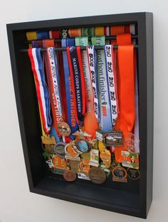 This satin black painted MDF display box has a slide-out plexiglass front as well as slide-out wooden dowels for hanging lots of running medals.