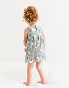 Baby girl so cute with her redhead ringlet curls. Wearing Winter Water Factory dress from Noble Carriage, made from organic cotton with adorable little patterns printed on. Navy blue High Seas illustrations detail this sleeveless white spring / summer dress. Nautical hipster babe style baby chic.