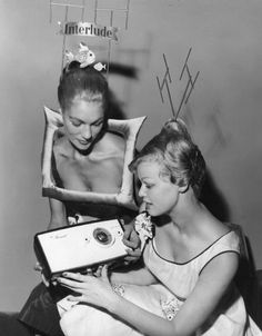 National Radio Show, 1957... Model Heather Wyatt (left), dressed as a television set, showing Eva Brann, Miss Sweden 1957, the Minuet Pains Portable Radio at the National Radio Show at Earl's Court, London. °