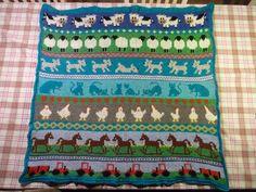 Babytæppe i uld med dyr og med bagside i turkis bomuldsstrik.