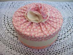 Caixa redonda revestida com tecido, tampa franzida e flor de tecido ao centro.
