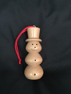 Small hand turned wooden snowman Christmas ornament. Made from solid red oak. Finished with multiple coats of polyacrylic and hung from red