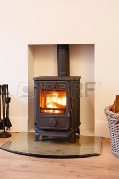 cosy: Cast iron wood burning stove in a modern contemporary fireplace Stock Photo