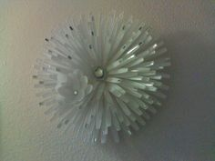 Flower wall decor made from handles of plastic spoons..
