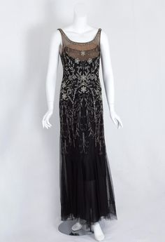 Beaded net evening dress, 1930s. The dazzling evening dress is constructed in layers. The under slip layer has a wide hem border of black chiffon and a bodice border of fine black net over nude chiffon. The torso of the outer layer is lavishly embellished with rhinestones, clear crystal beads, and tear-shaped crystals.