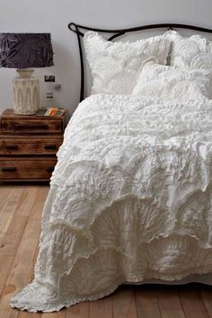 Bedroom with elaborate white bedspread. Luv the texture it brings to the room!