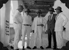 Five men, four in white suits. Expedition members Including Baum, Osgood in the middle, Bailey, Fuertes at far right and one other man, Cutting. Standing on an outdoor porch. 1927.