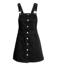 Siyah. Yıkanmış kottan, ayarlanabilir askılı, ön cepli, önü düğmeli, kısa tulum elbise.