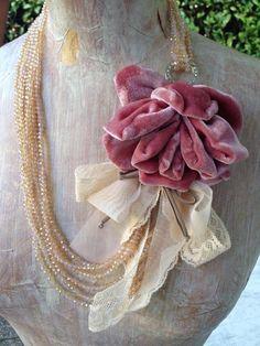 Donatella è una collana realizzata interamente in tessuto, confezionata con fili di lycra brillanti, boccioli di seta e piccole decorazioni in pizzo.