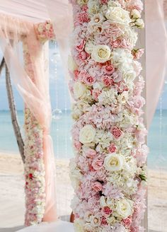 Overlooking the turquoise Bahamian waters, a pink and white arbor covered in…
