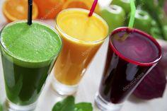 Foto com três sucos em fundo branco. Foco no topo dos copos e frutas desfocadas que os compõe no fundo.