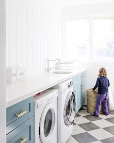 Beautiful laundry. Blue cabinets, black and white floor. Cottonwood Interiors.