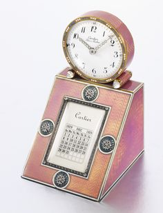 Enamel, moonstone and diamond desk clock, Cartier, 1908. The circular white enamel dial with Arabic numerals and millegrain-set diamond hands, within a grey and white enamel bezel, the feet accented with cabochon moonstones, on a rectangular silver base decorated with opalescent pink guilloché enamel and a sloping front calendar enhanced with grey enamel and rose diamond rosette motifs.