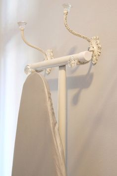 Hang your ironing board on two attractive hooks.