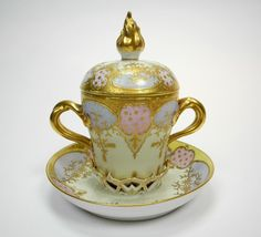 Royal Vienna two-handled covered cup and saucer with alternating cartouches of pink and blue with over gilding
