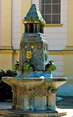 """Fountain Zolnay, Pécs, Hungary. Made in Zolnay Manufacture, 1912, by Andor Pilch. Erected: 1930.  Oxen-headed water-sprouts of the 4 m high fountain made of eosin, have been made by the pattern of one of the  drinking horn of the so-called golden find of Nagyszentmiklós. The fountain is erected on the place where in Turkish era had been the """"running of the Cadi"""". The square is named from 2003 Square Zolnay. (https://hu.wikipedia.org/wiki/Zsolnay-k%C3%BAt)"""
