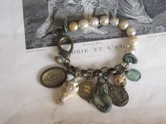 repurposed jewelry vintage pearl religious charm bracelet mermaid intaglio seashell pisces seaglass bone atelier paris on etsy. $79.00, via Etsy.