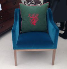 Luxe blue velvet chair with earthy green cushion.
