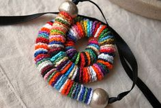 bracelet of tiny crocheted yo-yos with beads on the ends. colorful, simple.