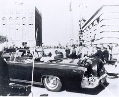 camelotdaydreams: This eerie photo depicts President Kennedy brushing back his hair as his limousine rounds the corner from Main St. to Houston St.
