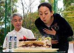 2010年9月26日、贈られたケーキに飾られたロウソクの火を吹き消す浅田真央。左は佐藤信夫コーチ