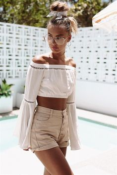 The boho and laid back Lilo Cropped Top is made from a lightweight fabric in a pale cream hue. It is an off shoulder, cropped design and features full length, flared sleeves and contrast ladder accent panels. Complete the look with a pair of high waisted shorts and tan choker. By Sabo Skirt.