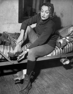 Marlene Dietrich In Germany. Actress Marlene Dietrich, 40, sporting Army sweater, knit cap & long wool underwear, sitting on bunk bed w. one GI boot off while putting on one of her gold pumps as she prepares to don her sequined evening gown to perform on stage during USO show. Location: Germany; Date taken: Feb. 27, 1945; Photographer: George Silk. USO Camp Shows, Inc. - ETO. | LIFE Photo Archive hosted by Google