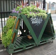 pot de fleurs vert en palettes de bois avec des plantes