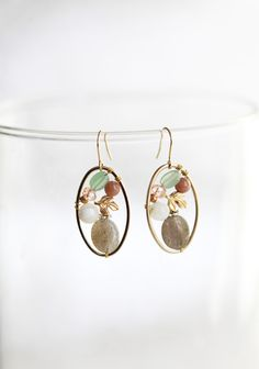 "Perfect Scenery Earrings 16.99 at shopruche.com. These earrings hold delicate ovals of a golden hue that encircle a cluster of softly colored stones, shimmering accents, and gold colored charms.1.5"" long"