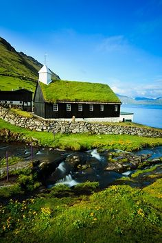Funningur, Eysturoy Island, Faroe Islands - A stream running into the Funningsfjordur and a traditional turf or grass roofed church, located in the picturesque village of Funningur.