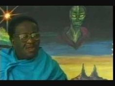 Credo Mutwa in front of a painting of a Chitauri.