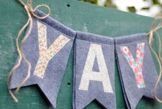 "Double-layered 5"" x 8"" gray premium felt chevron-style flags,  stitched with a variety of fun cotton fabric letters, strung onto 2 yards of jute twine."
