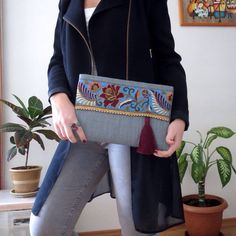 Ethnic Clutch, womens bag, boho bag, bohemian clutch, fashion clutch, gift for her  A fashion statement that everyone will swoon over! This floral clutch will bring elegance to your style. It will be chic with jeans or dresses and you may use this clutch bag both day and night. This clutch bag is perfectly handmade with high quality grey jute fabric. Designed with a silk bohemian embroidery and a tassel. Clutch has a burgundy silk satin interfacing and a padding inside to stand upright…