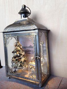 Metallic Lantern, House inside a Christmas scene with tree in shades of white and gold, white console shabby with edges in gold, polychrome birth, candles and garlands. The floor is covered by a hand-painted carpet. The lantern has led light with power switch 220.