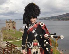 Piper poses near Urquhart Castle on Loch Ness, Scotland