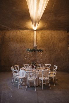 Beautiful table for the bride and the groom and their close family. I love the round garland hanging above it and the tiny lights on the golden wall behind. This is a wedding dream. If you need your wedding planned and style like this, we know the person to do it!