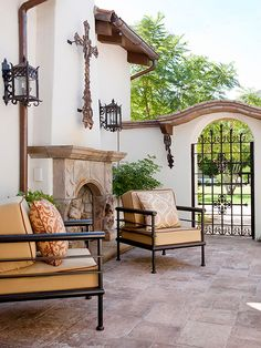 In this outdoor space, an archway with a wrought-iron gate helps to separate the front of the house from the backyard. A stone fireplace creates an ideal sitting place on breezy summer nights. Although the chairs have a modern look, they work with the rest of the space because of their dark color and Spanish-style patterned pillows.