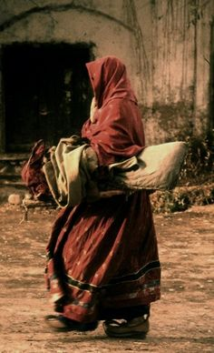 A Kuchi Nomad Woman, dressed in Traditional Kuch Attire, known as a Ghandh, walks towards her Tent with a bundle under her arm.